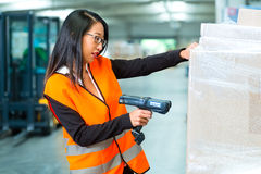 Worker scans package in warehouse of forwarding. Logistics - female worker or shipper with protective vest and scanner, scans bar-code of package, he standing at royalty free stock photo