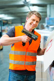 Worker scans package in warehouse of forwarding. Logistics - Warehouseman with protective vest and scanner, scans bar-code of package, he standing at warehouse Royalty Free Stock Photography