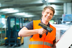 Worker scans package in warehouse of forwarding. Logistics - Warehouseman with protective vest and scanner, scans bar-code of package, he standing at warehouse Royalty Free Stock Photos
