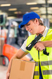Worker scans package in warehouse of forwarding. Warehouseman with protective vest and scanner, scans bar-code of package, he standing at warehouse of freight Stock Image