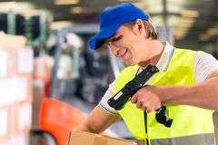 Worker scans package in warehouse of forwarding. Warehouseman with protective vest and scanner, scans bar-code of package, he standing at warehouse of freight Royalty Free Stock Photo
