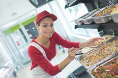 Worker scooping ordered food Stock Photos
