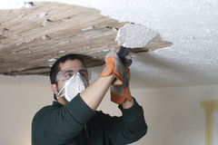 Ceiling Demolition Scrape. A worker scraping the ceiling and removing plaster from the lathe Royalty Free Stock Images