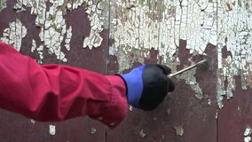 Worker scraping old paint from wooden wall Royalty Free Stock Images