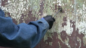 Worker scrapping old cracked paint from wooden door. Worker hand scrapping old cracked paint from wooden door