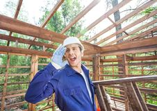 Worker Screaming While Carrying Ladder. Male worker screaming while carrying ladder at construction site Royalty Free Stock Photo