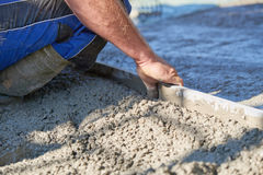 Worker screeding cement floor with screed Royalty Free Stock Photography