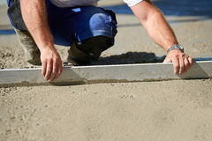 Worker screeding cement floor with screed. Mason building a screed coat cement Royalty Free Stock Photos