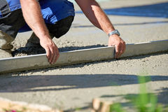 Worker screeding cement floor with screed Stock Photos