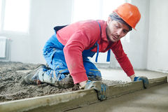 Worker screeding indoor cement floor with screed. Builder worker screeding indoor cement floor with screed at construction site Stock Photography