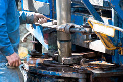 Worker screwing on a drill casing. A worker uses a large wrench to screw on a drill casing during the operation of a water well drill rig Royalty Free Stock Photography