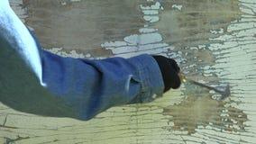Worker scrubbing off peeling paint, 4K stock video footage
