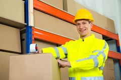 Worker Sealing Cardboard Box With Adhesive Tape Stock Photo