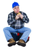 Worker seated on the toolbox. Eating a hamburger Stock Images