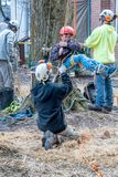 Worker securing a child into a tree harness. New Carlisle Indiana USA , March 17, 2019; During  this event  During sugar camp days at Bendix woods county park, a royalty free stock image