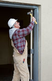 Worker Securing Door Frame Stock Photo