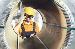 Worker seen through a steel sheet metal roll Royalty Free Stock Photography