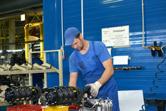 The worker selects depreciation racks for cars. Assembly shop of Stock Photo