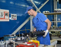 The worker selects depreciation racks for cars. Assembly shop of Royalty Free Stock Images
