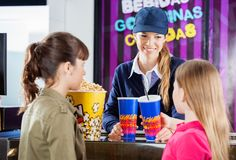 Worker Selling Snacks To Girls At Concession. Female worker selling drinks and popcorn to girls at cinema concession counter Stock Photo