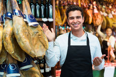 Worker selling Spanish jamon. And smiling in a delicatessen store Royalty Free Stock Image