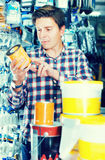 Worker selling tins of paint. Portrait of positive worker selling tins of paint in hardware shop Royalty Free Stock Photography