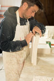 Worker Separating Plaster Model from Mold. A stubbly man in scruffy work clothing carefully separating a plaster model from its mold Royalty Free Stock Photography