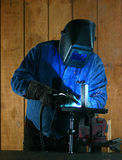 Worker Series. Metal worker welds two pieces of metal together Stock Image