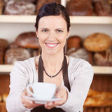 Worker serving coffee in a bakery Stock Images