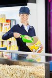 Worker Serving Popcorn In Bucket At Cinema Royalty Free Stock Photography