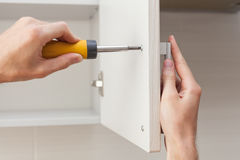 The worker sets a new handle on the white cabinet with a screwdriver. Stock Image