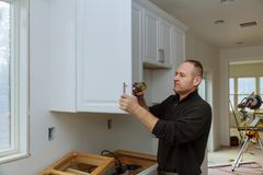 Worker sets a new handle on the white cabinet with a screwdriver installing kitchen cabinets. The worker sets a new handle on the white cabinet with a royalty free stock photos
