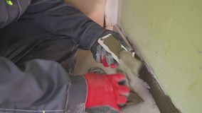 Worker sets small tiles on the wall in the kitchen. His hands are placing the tile on the adhesive. stedikam shooting. Worker sets tiles on the wall in the stock video