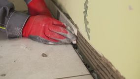 Worker sets small tiles on the wall in the kitchen. His hands are placing the tile on the adhesive. stedikam shooting. Worker sets tiles on the wall in the stock footage