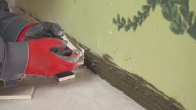 Worker sets small tiles on the wall in the kitchen. His hands are placing the tile on the adhesive. stedikam shooting. Worker sets tiles on the wall in the stock video footage