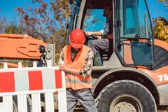Worker setting up earthworks construction site. Erecting fence royalty free stock image