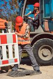 Worker setting up earthworks construction site. Erecting fence royalty free stock photo