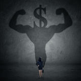 Worker with a shadow of strong athlete and dollar sign. Female entrepreneur looking at a shadow of athlete and a dollar currency head Stock Image