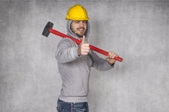 Worker shooing thumbs up. Yellow helmet on his head Royalty Free Stock Photography