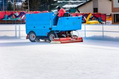 A worker is shooting a special ice maintenant machine at a sports rink. Cooking place for skating. ice preparation at the rink. Between sessions in the evening stock photos