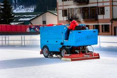 A worker is shooting a special ice maintenant machine at a sports rink. Cooking place for skating. ice preparation at the rink stock image
