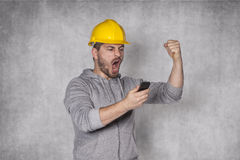 Worker shouting into the phone. On the grey background Royalty Free Stock Images