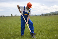 Worker with Shovel on a Green Lawn Stock Photography
