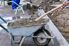 Worker shovels concrete from a wheelbarrow at curb block installation. Stock Image