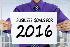 Worker showing business goals for 2016 in office Royalty Free Stock Image
