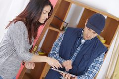 Worker showing customer details on paper Royalty Free Stock Photos