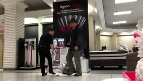 Worker showing Dyson cinetic vacuum for custmer. Inside The Bay store stock video