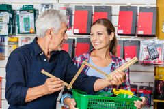 Worker Showing Folding Ruler To Customer In. Happy male worker showing folding ruler to customer in hardware store Royalty Free Stock Photography