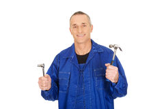 Worker showing his wrench and hammer. Happy mature worker showing his wrench and hammer Stock Photo