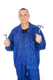 Worker showing his wrench and hammer. Happy mature worker showing his wrench and hammer Royalty Free Stock Photos